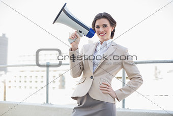 Charming stylish brown haired businesswoman holding a megaphone