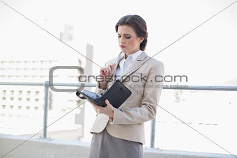 Frowning stylish brown haired businesswoman filling her schedule