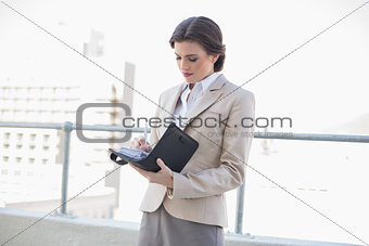 Concentrated stylish brown haired businesswoman filling her schedule
