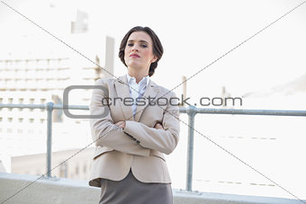 Attractive stylish brown haired businesswoman standing with arms folded