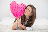 Beautiful casual brown haired woman in white pajamas kissing a heart shaped pillow