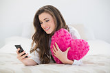 Content casual brown haired woman in white pajamas using her mobile phone