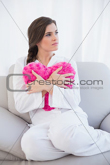 Thoughtful casual brown haired woman in white pajamas hugging a heart shaped pillow
