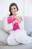 Pleased casual brown haired woman in white pajamas cuddling a heart shaped pillow