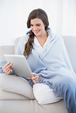 Beautiful casual brown haired woman in white pajamas shopping online with her tablet pc