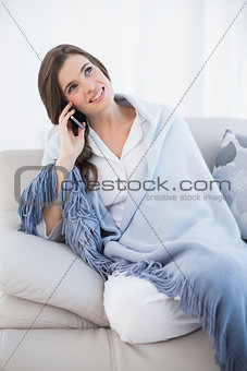 Pretty casual brown haired woman in white pajamas making a phone call