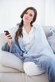 Attractive casual brown haired woman in white pajamas holding a mobile phone