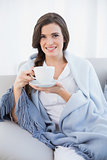 Happy casual brown haired woman in white pajamas holding a cup of coffee