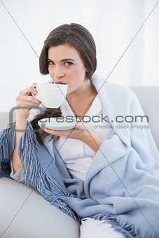 Peaceful casual brown haired woman in white pajamas drinking coffee