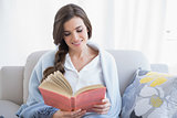 Peaceful casual brown haired woman in white pajamas reading a book