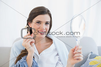 Charming casual brown haired woman in white pajamas holding an eyelash curler