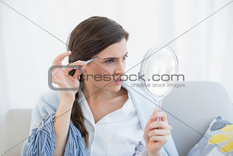 Focused casual brown haired woman in white pajamas plucking her eyebrows
