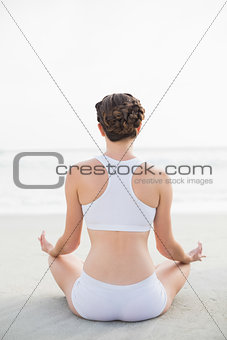 Attractive slim brown haired model in white sportswear meditating in lotus position
