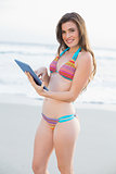 Pleased slim brown haired model in coloured bikini using a tablet pc