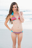 Happy slim brown haired model in coloured bikini making a phone call