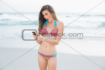 Amazed slim brown haired model in coloured bikini looking at her mobile phone