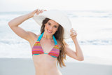 Pretty slim brown haired model in coloured bikini wearing a white hat