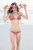 Amused slim brown haired model in coloured bikini playing with a flower necklace