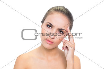 Annoyed young brunette woman looking at camera