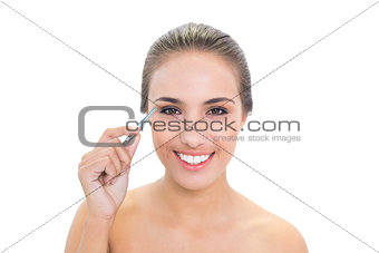 Smiling brunette woman plucking her eyebrows