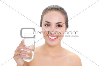 Smiling brunette woman holding a glass of water