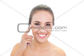 Smiling brunette woman pointing at her eye