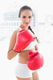 Sporty brunette woman wearing red boxing gloves