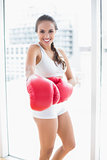 Cheerful sporty brunette wearing red boxing gloves
