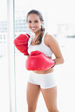 Happy sporty brunette wearing red boxing gloves