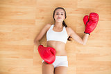 Sporty brunette woman looking at camera with red boxing gloves on