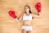 Sporty tired brunette wearing red boxing gloves