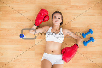 Tired brunette wearing red boxing gloves