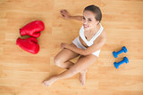 Smiling sporty brunette sitting next to red boxing gloves and dumbbells