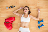 Sporty brunette lying next to jump rope red boxing gloves and dumbbells