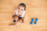 Smiling sporty brunette holding a mobile phone and sitting next to dumbbells