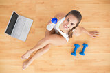 Sporty brunette holding a water bottle and sitting next to a laptop and dumbbells