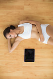 Content sporty brunette lying next to a tablet