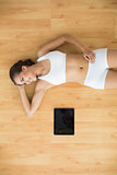 Young sporty brunette lying next to a tablet