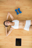 Relaxed sporty brunette lying next to a tablet and dumbbells