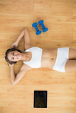 Happy sporty brunette lying next to a tablet and dumbbells