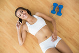 Laughing sporty brunette using a mobile phone and lying next to dumbbells