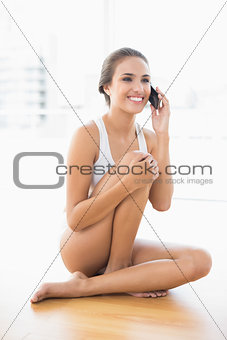 Laughing brunette sitting on the floor and using a mobile phone