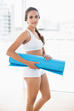 Content sporty brunette holding an exercise mat