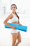 Content sporty brunette woman holding an exercise mat