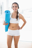 Happy sporty woman holding a balled up exercise mat