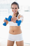 Happy sporty brunette using dumbbells