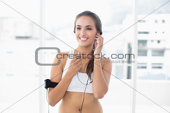 Attractive sporty brunette listening to music