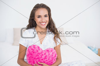 Smiling attractive woman holding heart pillow