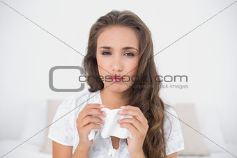 Tired beautiful brunette holding a tissue