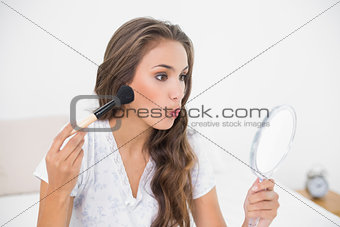 Attractive young brunette holding a brush and a mirror